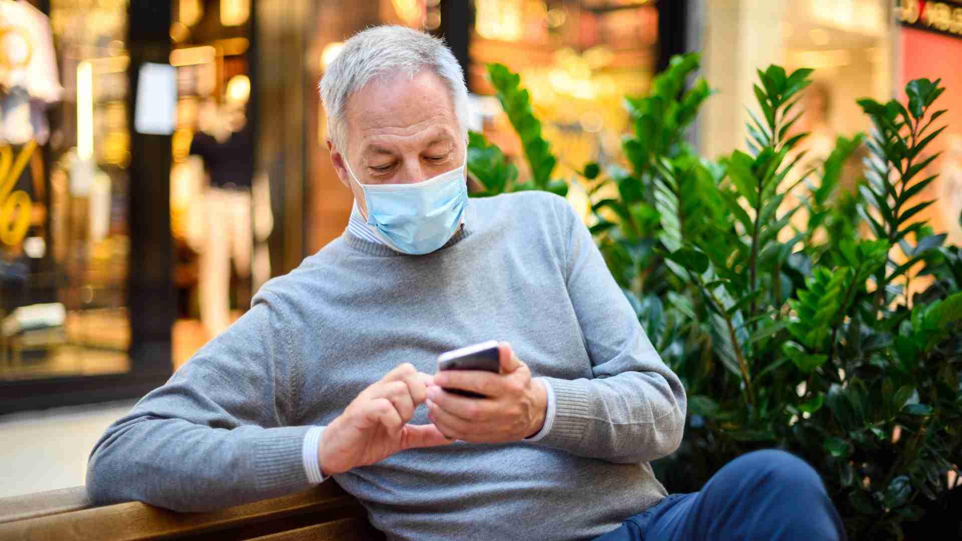 Senior Man sitting bench using-smartphone mall wearing Covid mask